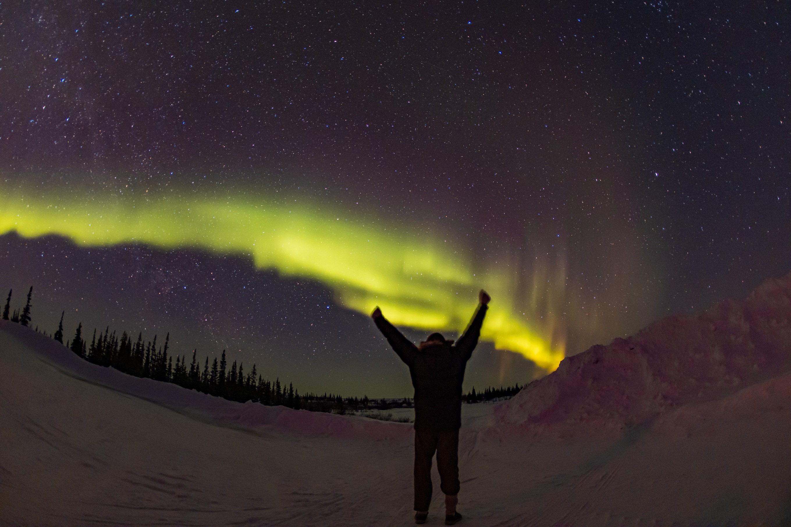 Ben standing in front of the northern lights and a star speckled sky. Churchill Manitoba, Canada